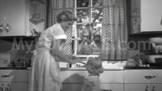 1950s Mother Gives Daughter a Glass of Water BW