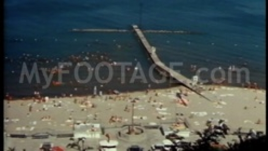 Long shot of crowded beach with old pier in summer