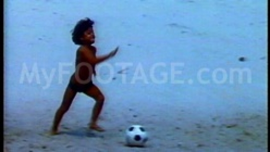 Quick clip of boy kicking a soccer ball at the beach