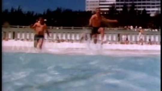 Two men run into the water and do a flying flip
